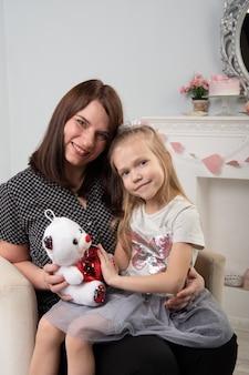 Madre e hija jugando con un oso de peluche en una pared gris. la hija se sienta en el regazo de las mamás. tradiciones familiares. familia feliz