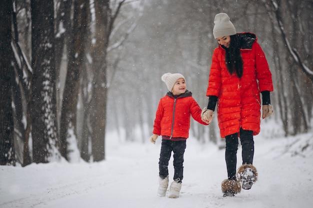 Madre e hija jugando en el parque de invierno
