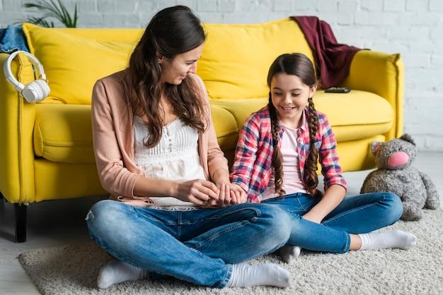 Madre e hija jugando en el piso