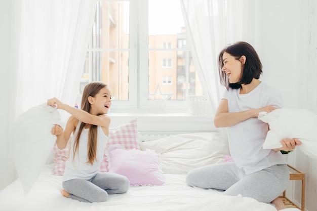 Madre e hija juguetonas se divierten juntas, pelean con almohadas en la cama, pasan tiempo libre en casa