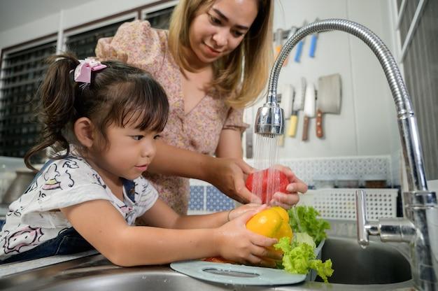 Madre e hija lavan verduras en la cocina