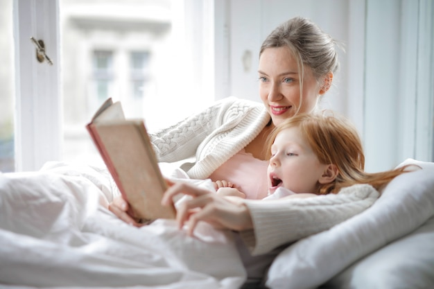 Madre e hija leen en la cama