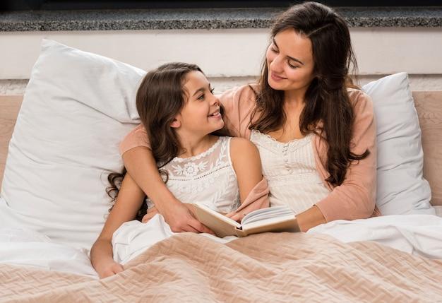 Madre e hija leyendo un libro en la cama