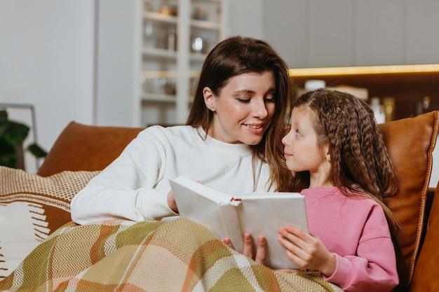 Madre e hija leyendo un libro en casa