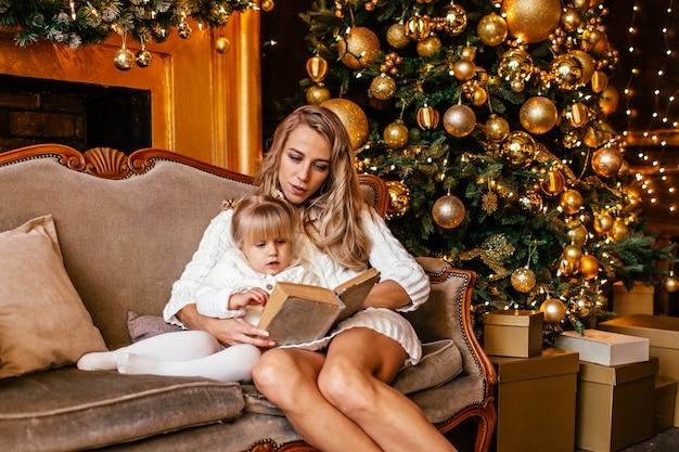 Madre e hija leyendo un libro en la chimenea en nochebuena. sala de estar decorada con árboles, chimenea y regalos. noche de invierno en casa para padres e hijos.