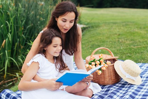 Madre e hija leyendo libro en picnic