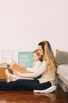 Madre e hija leyendo el libro en el piso