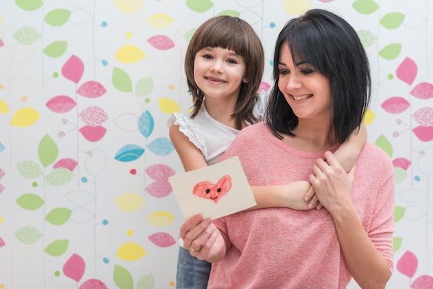 Madre e hija leyendo una pequeña tarjeta de felicitación