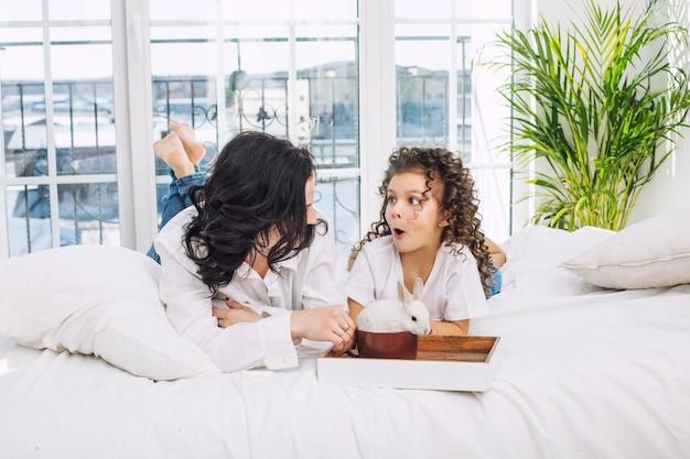 Madre e hija linda hermosa y feliz en la cama con conejo blanco en bandeja en el dormitorio