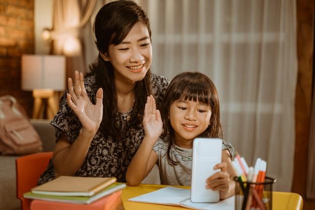 Madre e hija llamando con teléfono inteligente