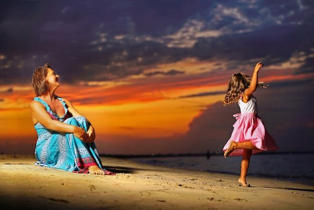 Madre e hija en el mar con puesta de sol