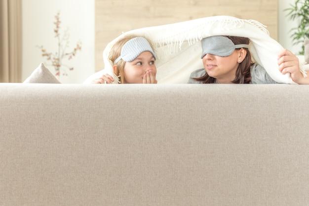 Madre e hija con máscara para dormir divirtiéndose en el sofá