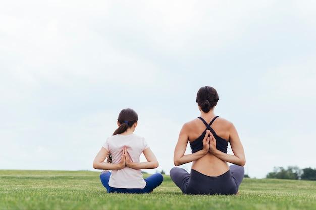 Madre e hija meditando por detrás