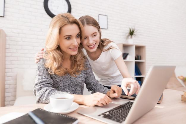 Madre e hija mirando en la computadora portátil en casa.