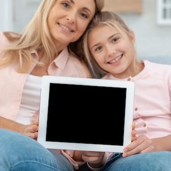 Madre e hija mostrando un marco simulado