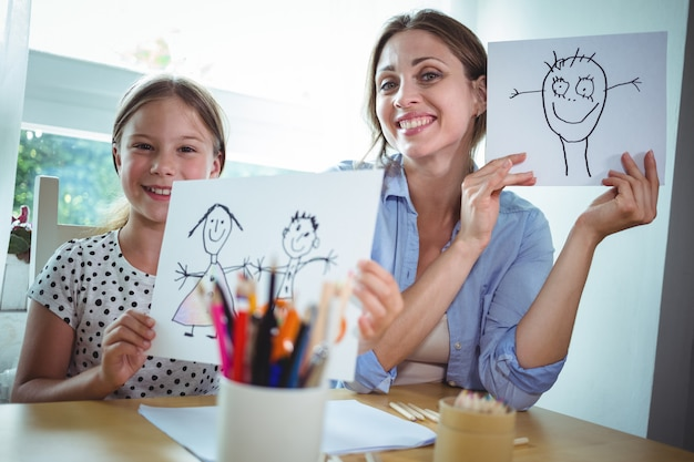 Madre e hija mostrando sus dibujos.