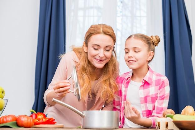 Madre e hija oliendo la comida preparada en la cocina.