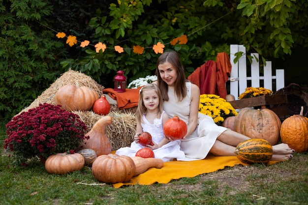 Madre e hija en otoño fondo con calabazas