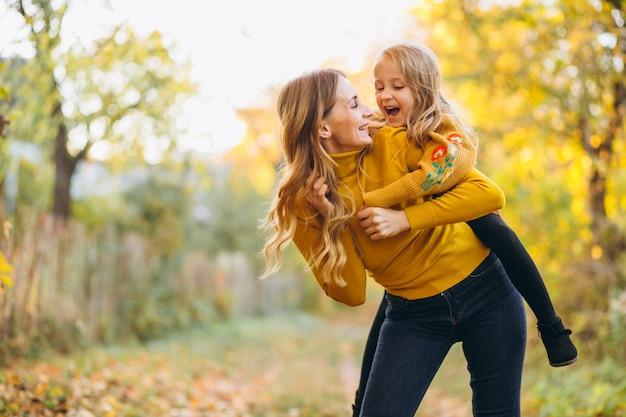 Madre e hija en el parque lleno de hojas