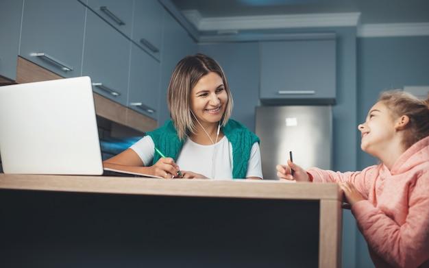 Madre e hija pasan tiempo en la cocina mientras los padres trabajan en la computadora portátil y el niño dibuja