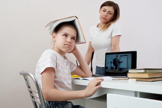 Madre e hija peleando por la tarea, la madre molesta está enojada con la pequeña hija aburrida, la educación en el hogar, la incomprensión