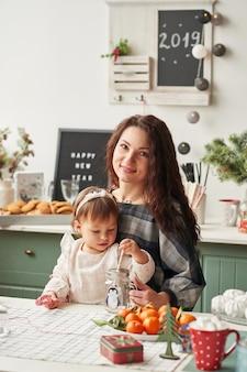 Madre e hija pequeña en la cocina decoradas para el año nuevo y navidad