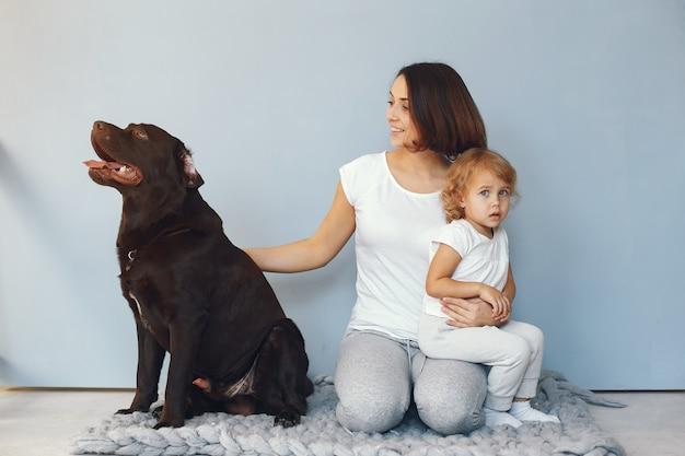 Madre e hija pequeña jugando con perro en casa