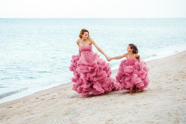Madre e hija pequeña en vestido rosa en la playa