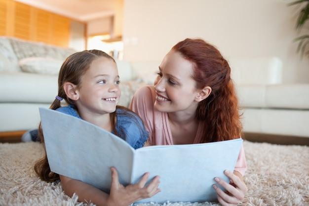 Madre e hija con periódico en el piso