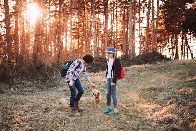 Madre e hija con perro en el bosque durante el atardecer