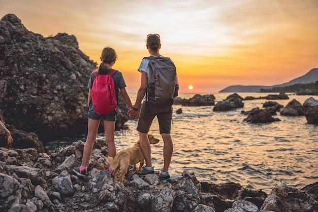 Madre e hija con un perro caminando por la orilla del mar