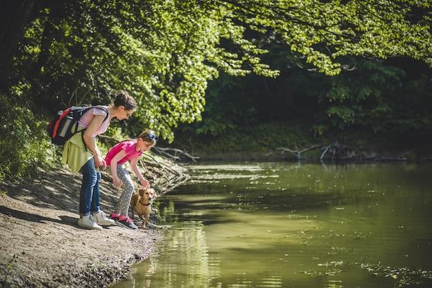 Madre e hija con perro junto al lago