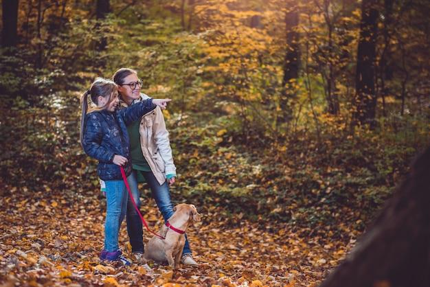 Madre e hija con perro senderismo en un bosque