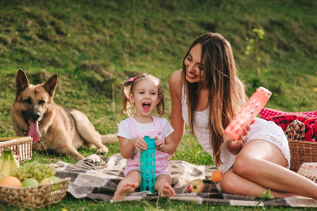 Madre e hija en un picnic con un perro