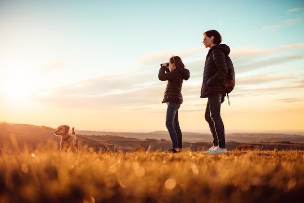 Madre e hija de pie en la cima de la montaña con perro y usando binoculares