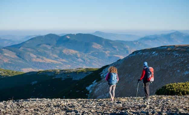 Madre e hija de pie en la cresta de la montaña