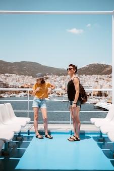 Madre e hija de pie en la cubierta del ferry