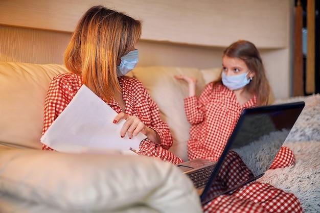 Madre e hija en pijama con cuaderno y papeles trabajando desde casa con máscara protectora
