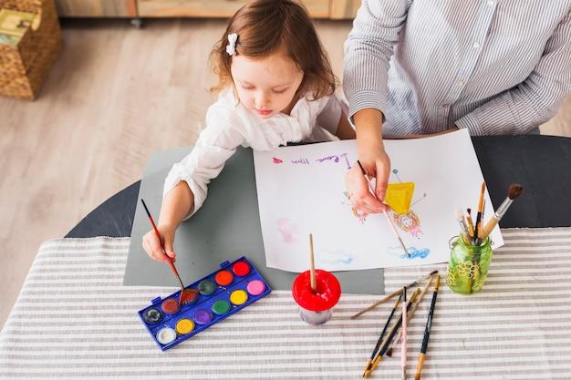 Madre e hija pintando en hoja de papel