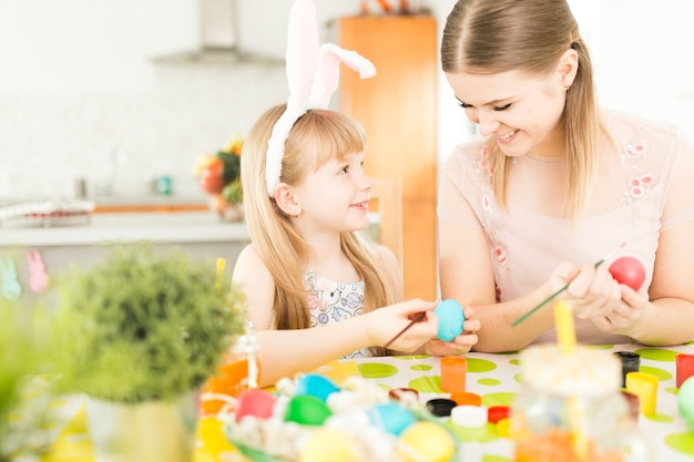 Madre e hija pintando huevos