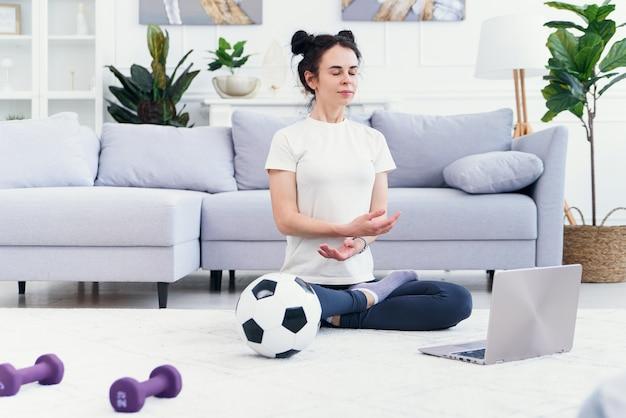 Madre e hija practicando clases de yoga en línea en casa durante el período de aislamiento de cuarentena durante la pandemia de coronavirus. familia haciendo deporte juntos en línea desde casa. estilo de vida saludable