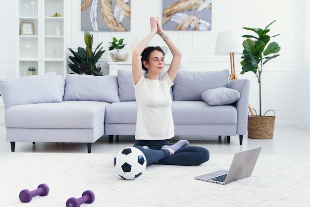 Madre e hija practicando clases de yoga en línea en casa