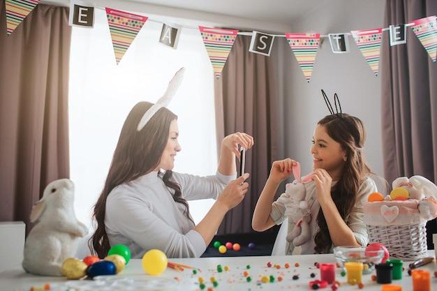 Madre e hija se preparan para la pascua. joven tomar foto de niña con juguete de conejo. chica pose. llevan orejas de conejo de pascua. la gente se sienta en la sala a la mesa.