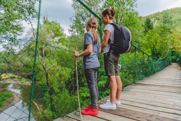 Madre e hija en puente colgante de madera