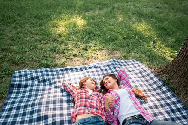 Madre e hija que llevan a cabo su mano que miente en la manta en parque