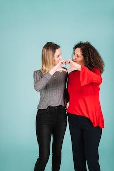 Madre e hija que muestran gesto de corazón