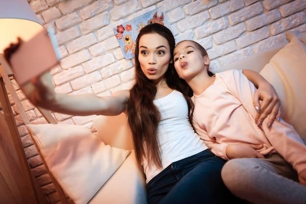 Madre e hija que toman el selfie en el teléfono en la noche en casa.