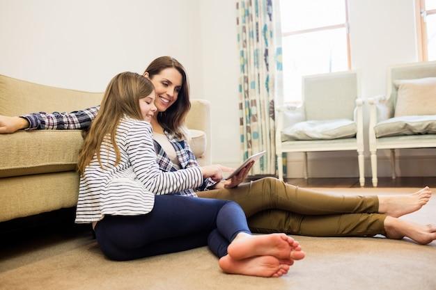 Madre e hija que usa la tableta digital en la sala de estar