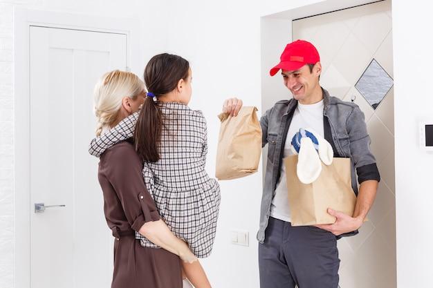Madre e hija reciben pedido del repartidor, entrega de juguetes y artículos para niños en el hogar