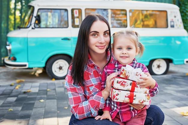 Madre e hija con regalos en el parque contra una furgoneta retro